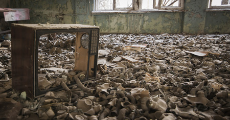 Gas masks on the floor with an old television in an abandoned middle school in Pripyat - Chernobyl nuclear power plant zone of alienation Stock Photo