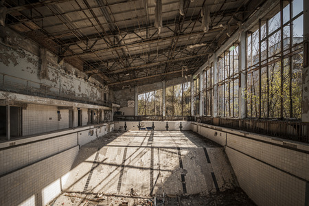 pripyat: Wide-angle view of an abandoned swimming pool of Pripyat. Chernobyl nuclear power plant zone of alienation Stock Photo