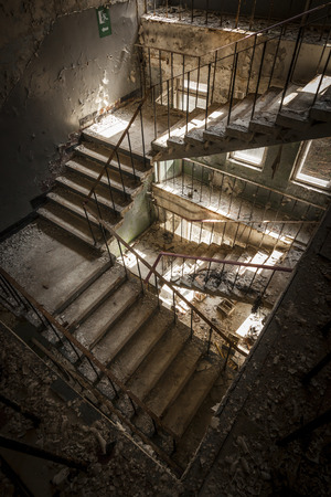 Concrete stairs illuminated with a picturesque light in an abandoned building in a sunny day. The light enters through some windows Banco de Imagens