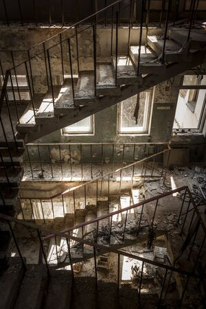 ghost town: Concrete stairs illuminated with a picturesque light in an abandoned building in a sunny day. The light enters through some windows Stock Photo