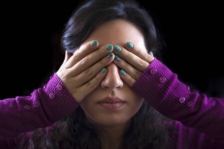 claustrophobia: Woman covering her eyes with her hands on a black background Stock Photo