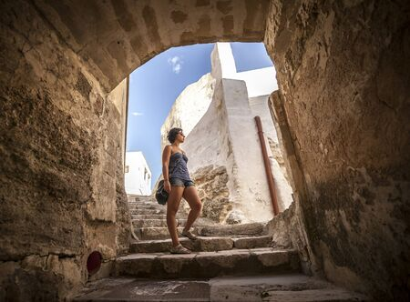 rupestrian: Girl is walking downstairs to under arc and between typical white buildings in a street of Ginosa, a south italian village similar to Matera.