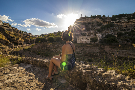 rupestrian: Girl look at the sun during sunset sitting on a low wall along an old street in Ginosa, a typical south italian village similar to Matera