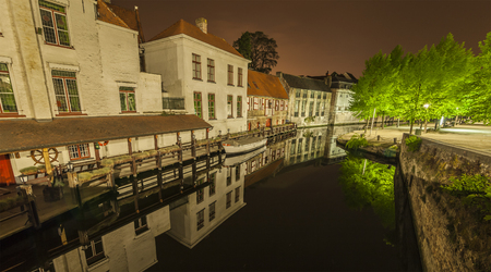 nocturnal: Romantic nocturnal view of a canal in Bruges. Buildings, trees and boats are reflected in the water