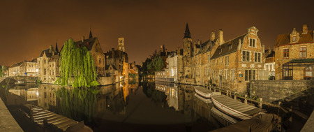nocturnal: Panoramic nocturnal and iconic view of historic medieval buildings along a canal from the Rozenhoedkaai in Bruges, Belgium. Buildings, trees and boats are reflected in the water