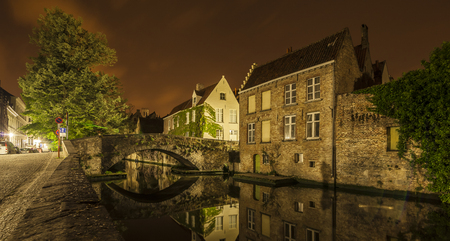 Romantic nocturnal view of a canal in Bruges. Buildings, trees and the bridge are reflected in the water