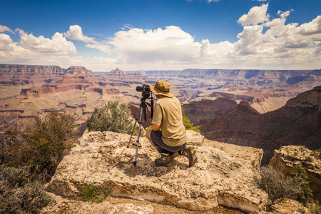 Photographer with reflex and tripod takes a photo of a panoramic view of the Grand Canyon  Banco de Imagens