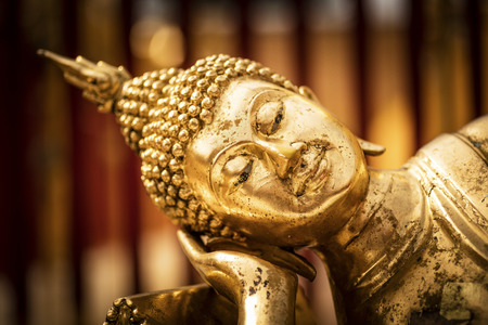 Face of a golden Tuesday Buddha statue at Doi Suthep Temple (Chiang Mai - Thailand)