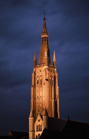 Belfry of the Church of Our Lady, Bruges (Belgium). Nocturnal image Standard-Bild