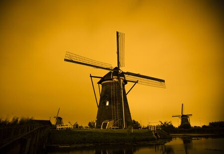 Picturesque landscape with windmills in Kinderdijk (Holland) at sunset