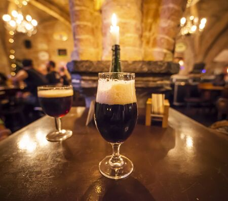 Two glasses of craft beer and a romantic candle in a typical belgian pub Standard-Bild