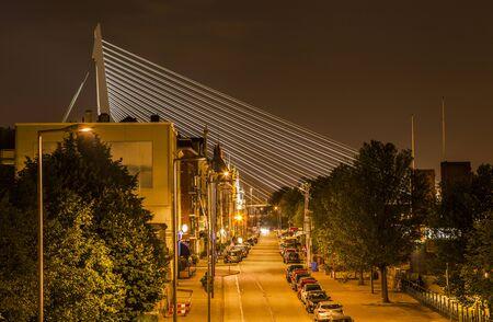 A night street in Rotterdam with the Erasmus Bridge on background