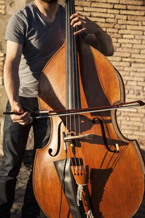 Musician playing the cello outside in a sunny day
