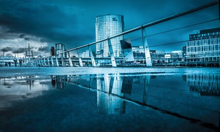 Belfast architecture along River Lagan reflected in a puddle. Belfast, Northern Ireland, United Kingdom