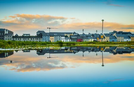 Beautiful panoramic sunset view reflected on a puddle in Galway city, Ireland