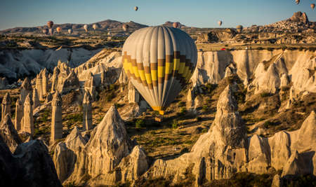 Cappadocia, Turkey, August 13, 2019: Hot air balloon flying over rock landscape