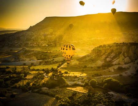 Cappadocia, Turkey, August 13, 2019: Hot air balloon flying over rock landscape