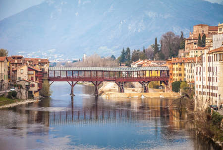 Bridge Ponte degli Alpini at river Brenta in Bassano del Grappa, Italy. Panoramic view at old town with vintage building and wooden bridge Editorial