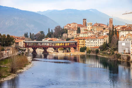Bridge Ponte degli Alpini at river Brenta in Bassano del Grappa, Italy. Panoramic view at old town with vintage building and wooden bridge