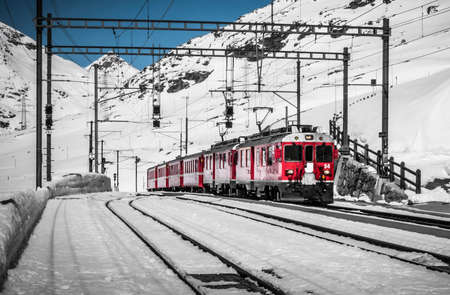 Bernina Express train, one of the highest railway in the world, goes across a little bridge in snowy mountain near a frozen lake