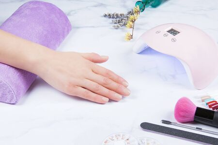 Closeup view of female hand with fresh beautiful modern gel polish manicure. With led uv lamp for curing top cover of nailpolish. White Marble background and stylish trendy manicure accessories.
