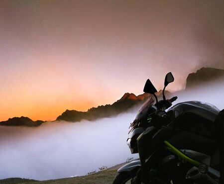 Motorcycle watching the golden sunset from the top of the mountain with thick fog.