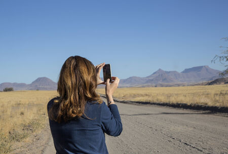 girl turist in Namibia photographing