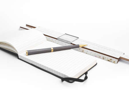 Vintage Desk with old and used slide rule, block notes and pen isolated on white background Stock Photo - 14129004