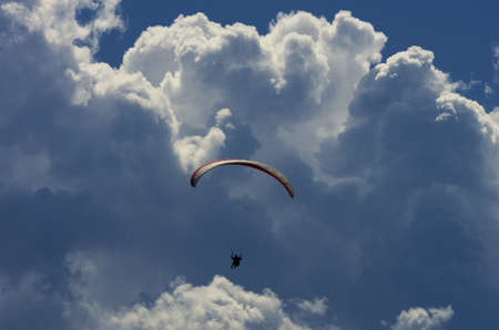 Paraglider with dramatic sky and huge clouds Stock Photo