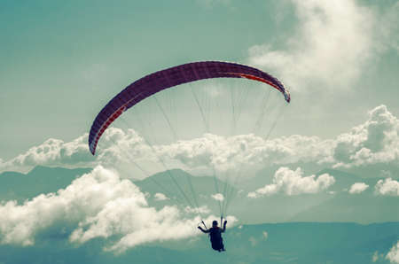 Paraglider over Alps with Clouds on Background