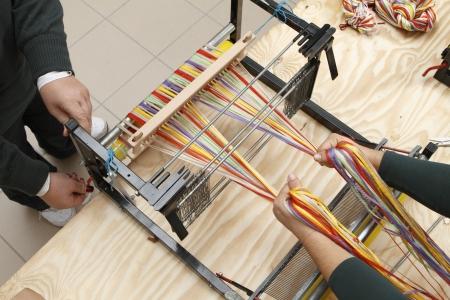 weavers: two weavers working on a loom Stock Photo