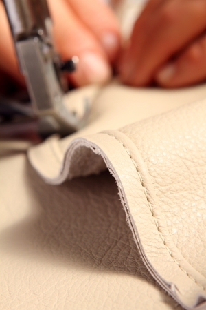 sew: hands of a craftsman while sewing leather