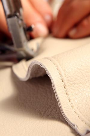 cuir: mains d'un artisan tout en cuir � coudre