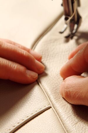 hands of a craftsman while sewing leather photo