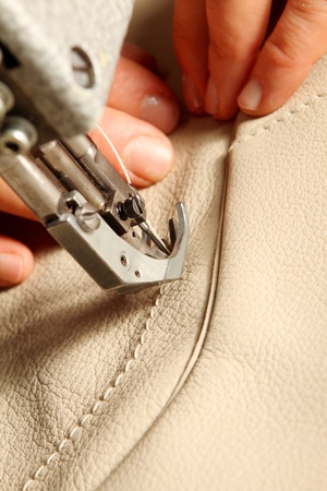 expertize: hands of a craftsman while sewing leather