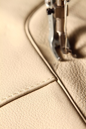 expertize: sewing machine in action for working leather for a sofa