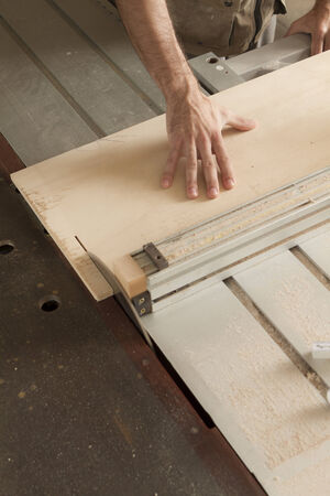 circular saw: hands of a worker while cutting with circular saw Stock Photo