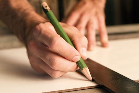 joinery: close-up di mani di una falegnameria durante la misurazione e la marcatura del legno che funziona