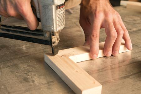 adjuntar: carpinter�a utiliza una pistola de clavos para unir piezas de madera
