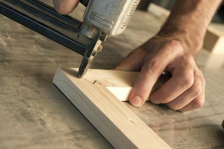 joinery: falegnameria utilizza una pistola sparachiodi per fissare pezzi di legno