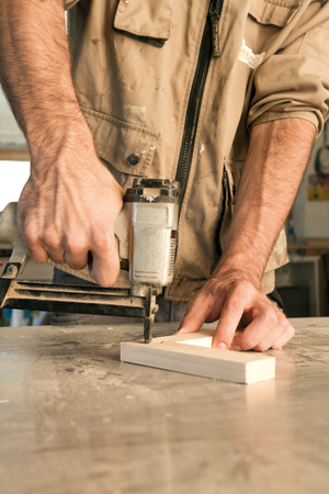 attach: joinery uses a nail gun to attach pieces of wood