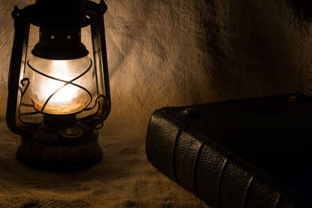 Set with an old rusty lantern and a book photo