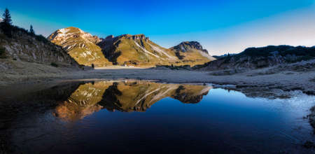 Mountains reflected in a small lake photo