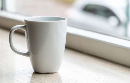 White mug on a marmer counter next to window light. with copy space left over for text and images.