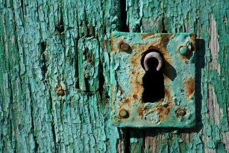 rusted lock on green wooden door Stock Photo