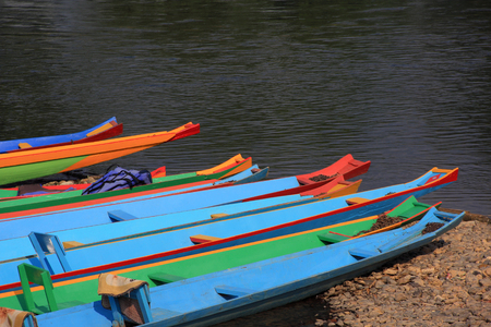 head of colorful long-tailed boats at riverside photo