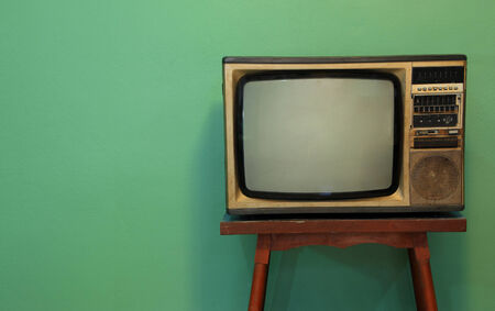 A retro TV on old wooden table with green paint wall background Stock Photo