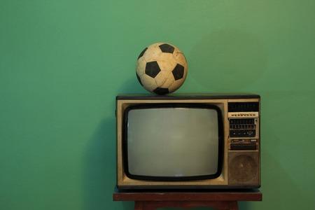 television antigua: Una vieja pelota de fútbol en un televisor retro con retro pared pintura verde Foto de archivo