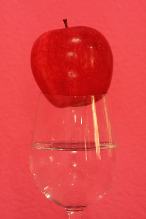 shocking: Red apple on a glass with shocking pink background