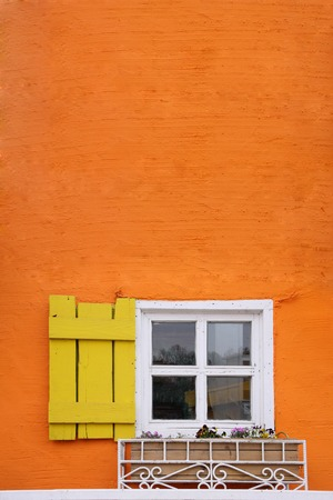 white frame and yellow panel window on orange wall photo